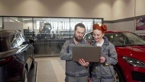 Duplexmechaniker, die den Laptop, arbeitend an der Garage verwenden stock footage