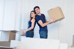 Durée neuve Les couples dans l'amour se déplaçant et maintiennent une boîte dans ses mains et Photo stock