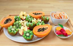 Durée toujours 1 Un plateau avec la papaye, kiwi, pommes Morceaux de mandarines et de pastèque dans des plats photos libres de droits