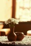 Durée toujours 1 Un vase brun à argile avec le chrysanthème se tient sur une table avec une nappe blanche dans le hall de restaur Image libre de droits