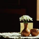 Durée toujours 1 Un vase brun à argile avec le chrysanthème se tient sur une table avec une nappe blanche dans le hall de restaur Image stock
