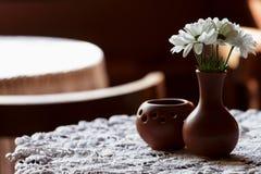 Durée toujours 1 Un vase brun à argile avec le chrysanthème se tient sur une table avec une nappe blanche dans le hall de restaur Photographie stock libre de droits