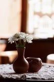 Durée toujours 1 Un vase brun à argile avec le chrysanthème se tient sur une table avec une nappe blanche dans le hall de restaur Photos libres de droits