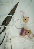 Durée toujours 1 vieux ciseaux rouillés, bobines de fil et dentelle sur le tissu blanc Plan rapproché Vue supérieure Images stock