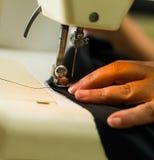 Dur labeur à faire, machine à coudre et mains de tailleur Tissu foncé Images libres de droits