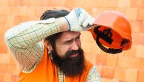 Dur labeur à un chantier de construction Profession lourde Le constructeur masculin essuie la sueur du front Constructeur fatigu? image libre de droits