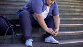 Dur pour que le gros jeune homme attache des dentelles, les personnes obèses de défis font face à chaque jour photo libre de droits