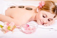 Durante el masaje de piedra de la terapia de los procedimientos del balneario la muchacha bonita rubia que se divierte observa la Imágenes de archivo libres de regalías