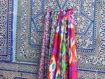Durante headscarfs tradicionais coloridos em uma parede colorida e decorada cerâmica em uma construção religiosa em Usbequistão Imagens de Stock