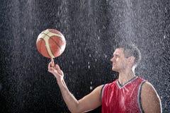Bola de giro do jogador de basquetebol em uma chuva grande Imagem de Stock