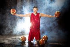 O jogador de basquetebol ajoelha-se para baixo com as bolas em seus braços Foto de Stock Royalty Free