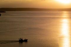 Durante puesta del sol, una pequeña gabarra navega el lago imagen de archivo
