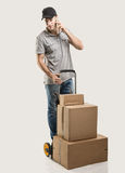 Durante una llamada - cajas y paquetes del camión de mano del mensajero Foto de archivo