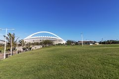 Grass Lawn Recreational Area against Moses Mabhida Stadium. DURBAN, SOUTH AFRICA - FEBRUARY 2018: Early morning empty grass lwn recreational area against Moses Stock Photography