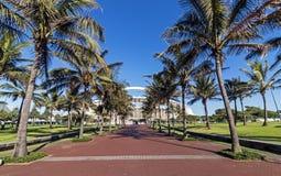 Palm Tree Lined Walkway Leading Towards Moses Mabhida Stadium. DURBAN, SOUTH AFRICA - FEBRUARY 23, 2018: Morning empty palm tree lined paved walkway leading Stock Photos