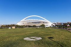 Empty Green Lawn Against Moses Mabhida Stadium. DURBAN, SOUTH AFRICA - FEBRUARY 23, 2018: Morning view of empty green lawn against Moses Mabhida stadium and Royalty Free Stock Photo
