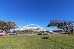 Green Lawn and Trees against Moses Mabhida Stadium. DURBAN, SOUTH AFRICA - FEBRUARY 23, 2018: Morning view of empty green lawn and trees against Moses Mabhida Royalty Free Stock Photo