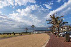 Paved Promenade Against Coastal Landscape and Blue Cloudy Sky royalty free stock images