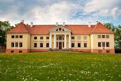 Durbe manor house near Tukums, Latvia. Durbe manor house near Tukums, Latvia with dandelion field in front Stock Image