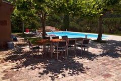 Durch das Pool; Tabelle und Stühle im Schatten der Platanen Stockfotografie