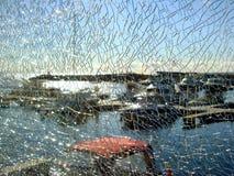Durch das zerbrochene Glas, das den sichtbaren Pier, die Boote parkend einzäunt Stockbilder