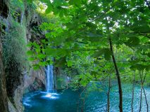 Durch die Blätter können Sie sehen wie der Fall des Wassers schön in den blauen See lizenzfreie stockfotografie