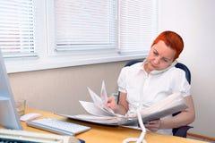 Durch die Dokumente schauen, der MädchenBürovorsteher, der am Telefon spricht lizenzfreie stockfotos