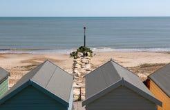 Durch die Strandhütten, entlang der Leiste und heraus zum Meer schauen Stockfotografie