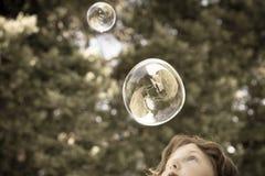 Durchbrennenluftblasen des jungen Mädchens Stockbilder