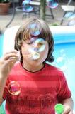 Durchbrennenluftblasen des kleinen Jungen Lizenzfreie Stockfotografie