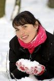 Durchbrennenschnee der jungen, schönen Frau in Richtung zur Kamera auf Winterhintergrund Lizenzfreie Stockfotografie