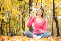 Durchbrennenseifenluftblase der Frau im Herbstpark Stockfotos