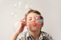 Durchbrennenseifenluftblasen des Jungen auf Weiß Lizenzfreie Stockfotos