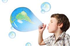 Durchbrennenseifenluftblasen des Jungen auf Weiß Lizenzfreie Stockfotografie