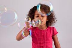 Durchbrennenseifenluftblasen des kleinen afrikanischen asiatischen Mädchens Stockbilder
