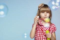 Durchbrennenseifenluftblasen des kleinen Mädchens Stockfotos