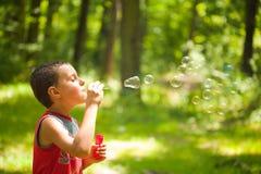 Durchbrennenseifenluftblasen des netten Kindes Lizenzfreie Stockfotos