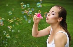 Durchbrennenseifenluftblasen des schönen jungen Brunettemädchens Stockfoto