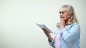 Durchdachte ältere Dame unter Verwendung der Tablette, Online-Banking App, moderne Technologien stockbild