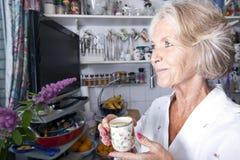 Durchdachte ältere Frau, die beim Halten der Kaffeetasse in der Küche weg schaut Lizenzfreie Stockfotografie