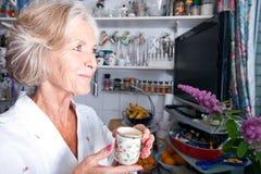 Durchdachte ältere Frau, die beim Halten der Kaffeetasse in der Küche weg schaut Stockbilder