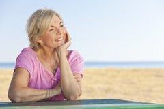 Durchdachte ältere Frau, die draußen am Tisch sitzt Lizenzfreies Stockbild