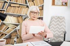 Durchdachte ältere Frau, die e-Lernen versucht lizenzfreie stockfotos