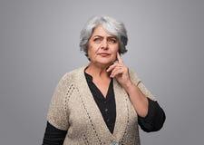 Durchdachte ältere Frau, die oben schaut stockbild