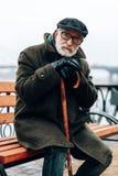 Durchdachte ältere männliche Person, die auf der Bank sitzt lizenzfreies stockfoto