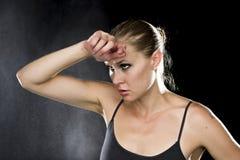 Durchdachte athletische Frau mit der Hand auf Stirn Lizenzfreie Stockfotografie