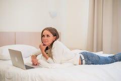 Durchdachte attraktive blonde Frau, die eine Laptop-Computer verwendet, wie sie am Rand eines Betts zu Hause oder in einem Hotels Stockbild