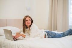 Durchdachte attraktive blonde Frau, die eine Laptop-Computer verwendet, wie sie am Rand eines Betts zu Hause oder in einem Hotels Stockfotos