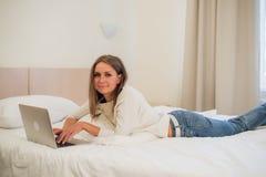 Durchdachte attraktive blonde Frau, die eine Laptop-Computer verwendet, wie sie am Rand eines Betts zu Hause oder in einem Hotels Lizenzfreie Stockbilder