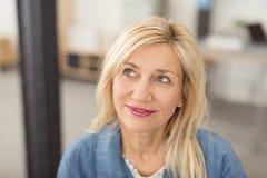 Durchdachte attraktive Frau von mittlerem Alter Stockfotos